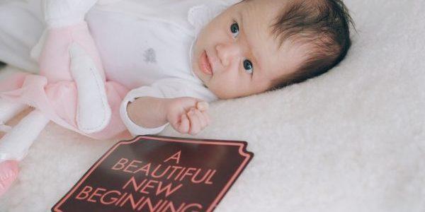 """Zoey liegt auf einem Kissen. Neben ihr liegt ein Schild, wo """"a beautiful new beginning"""" drauf steht."""