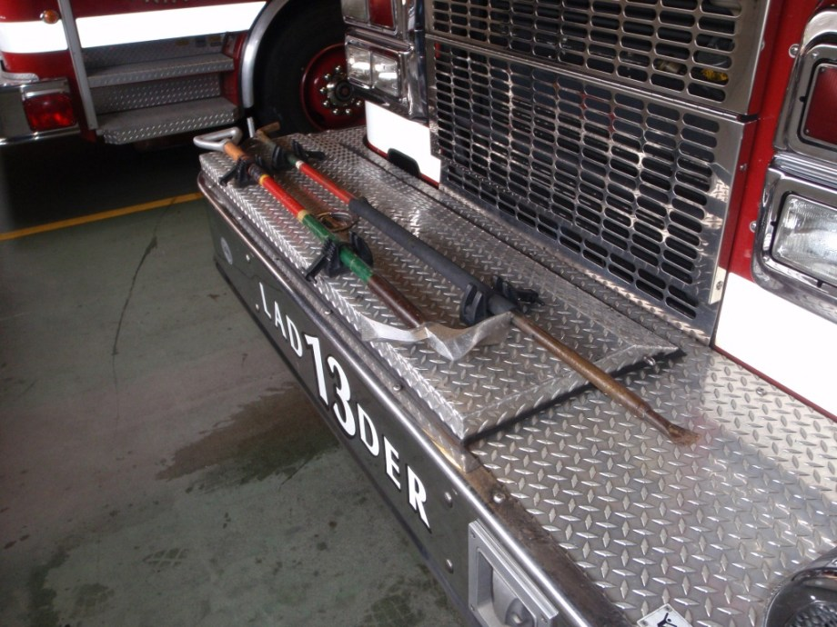 "One example of Truck 13's front bumper ""hood ornament,"" a 6' NY Roofman's Hook and a 4' D-handled Hawk Phase II prototype."