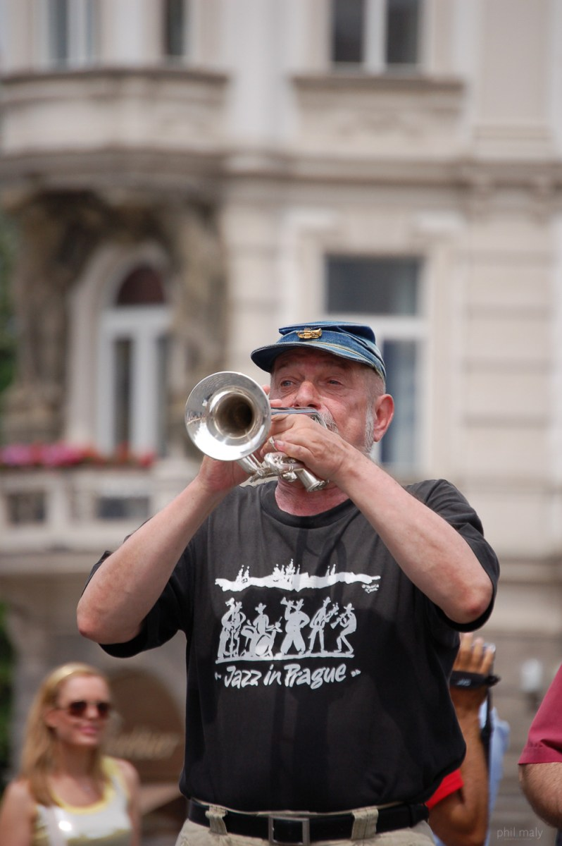 Street portrait of an old man playing trumpet