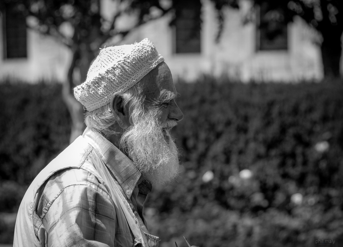 Street portrait of an old man with a long white beard smiling