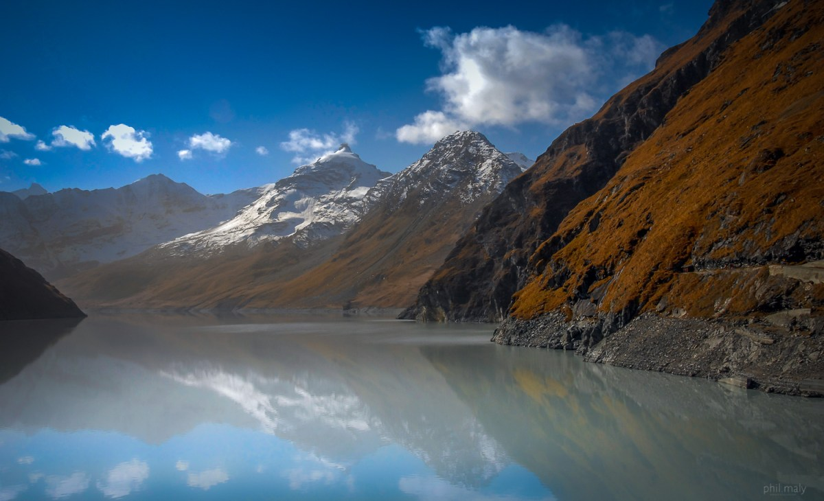 Snow capped summits reflecting in the lake of the Grande Dixence dam