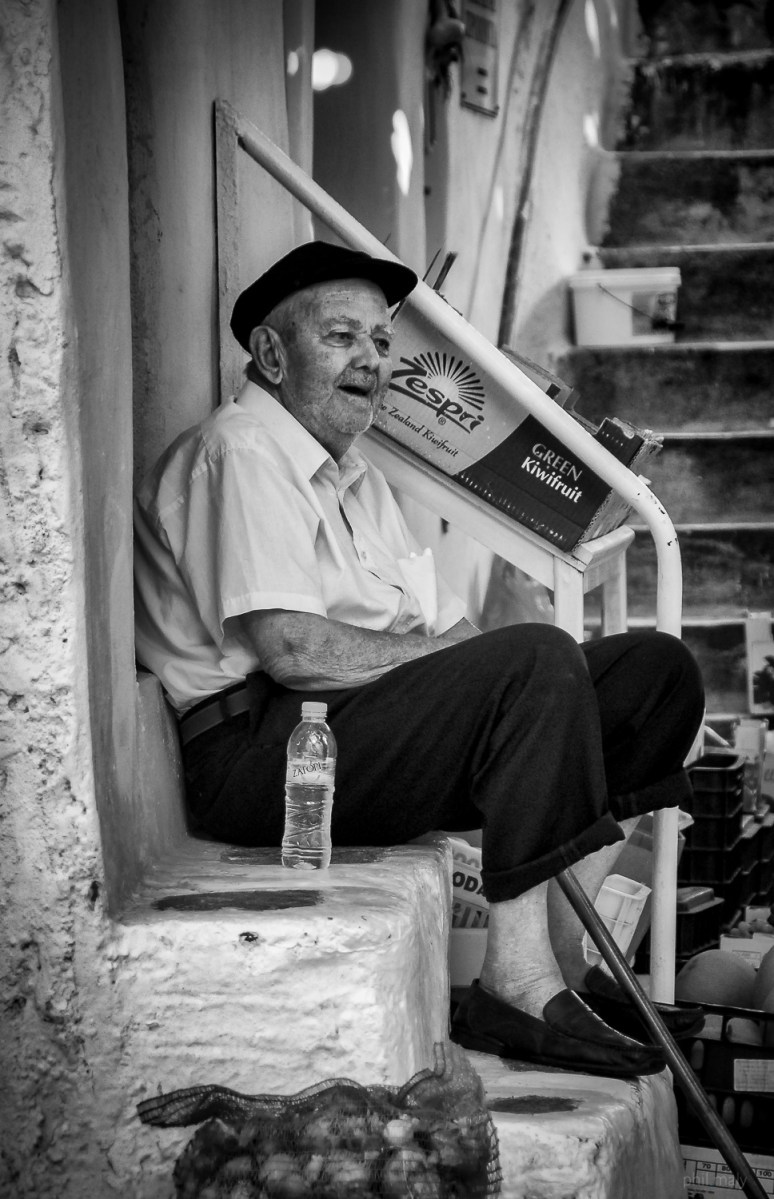 Street portrait of an old man sitting on the stairs in front of his house