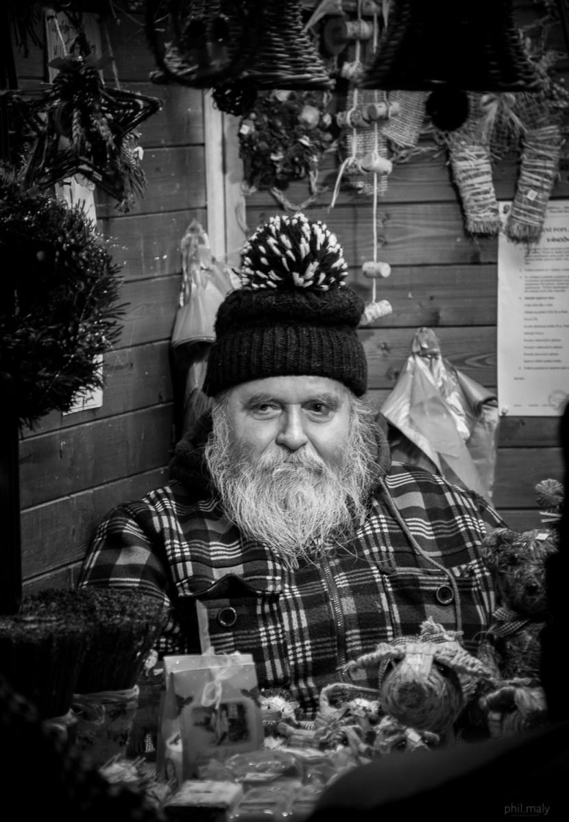 Street portrait of an old man in a wooden cabin looking like Santa Claus