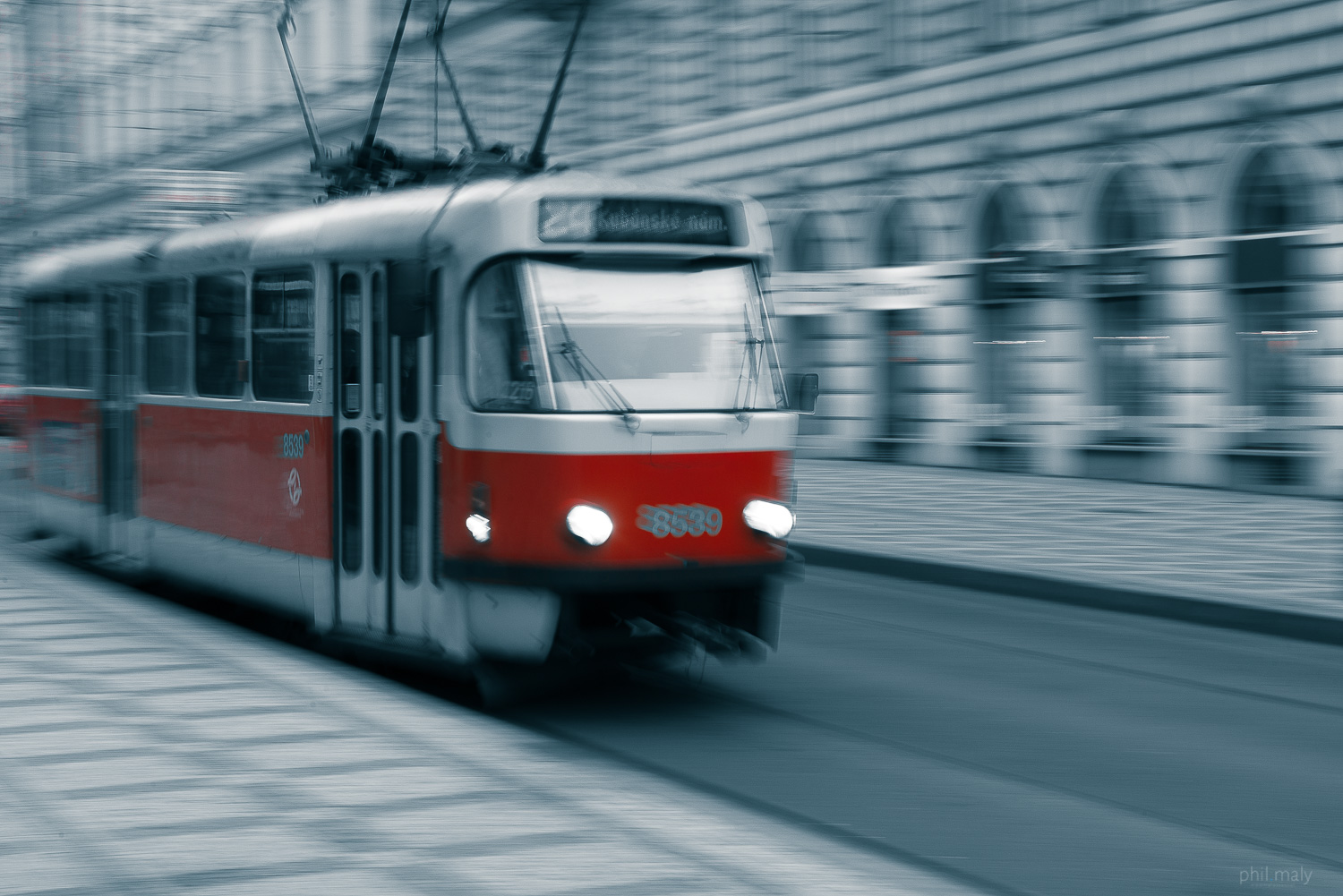 Panning shot of a red streetcar in the city of Prag