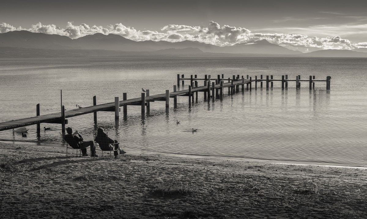 People chilling on the beach of Préverenges in front of the lake Leman with a wooden pier and the mountains in the background