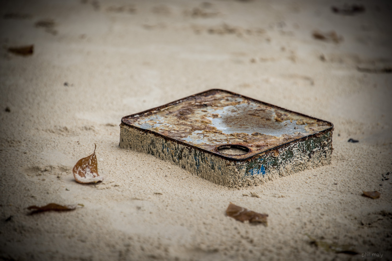 Detail of a metallic can dug in the sand of a beach