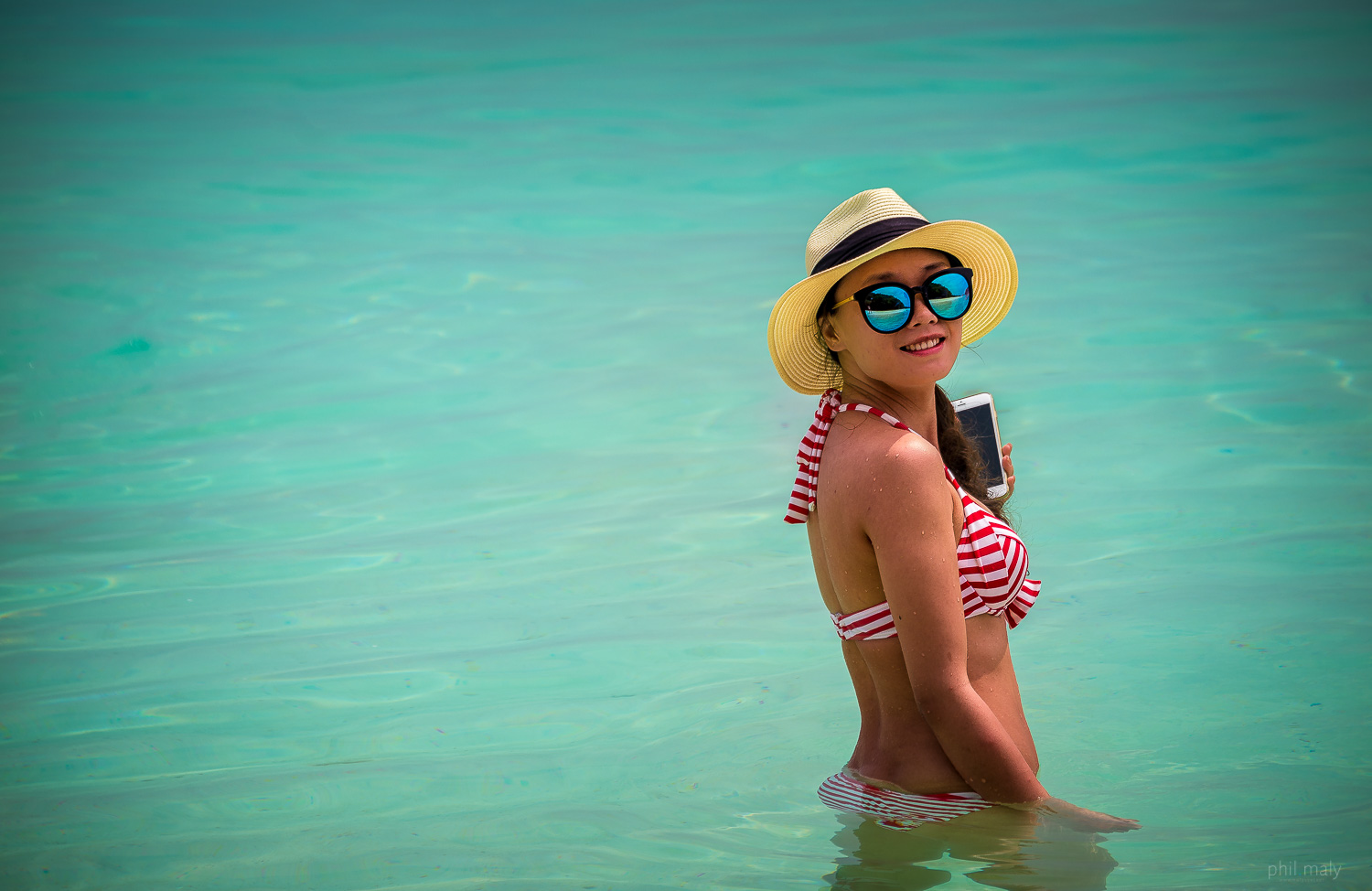 Portrait of a girl with a red stripped swimsuit in the water with her iPhone