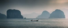 Longtail boat with the islands of the Phang Nga bay in the background