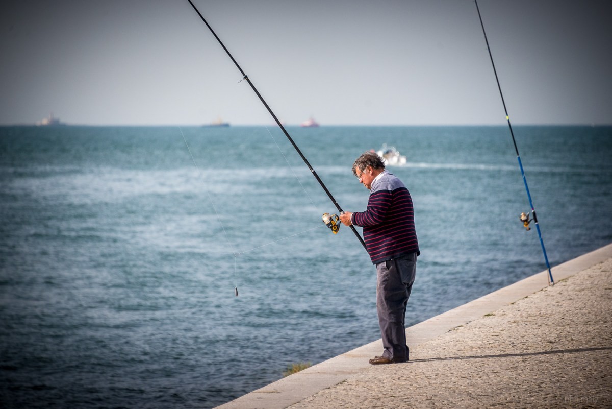 Fisherman with his fishing rod at the waterfront of Belem