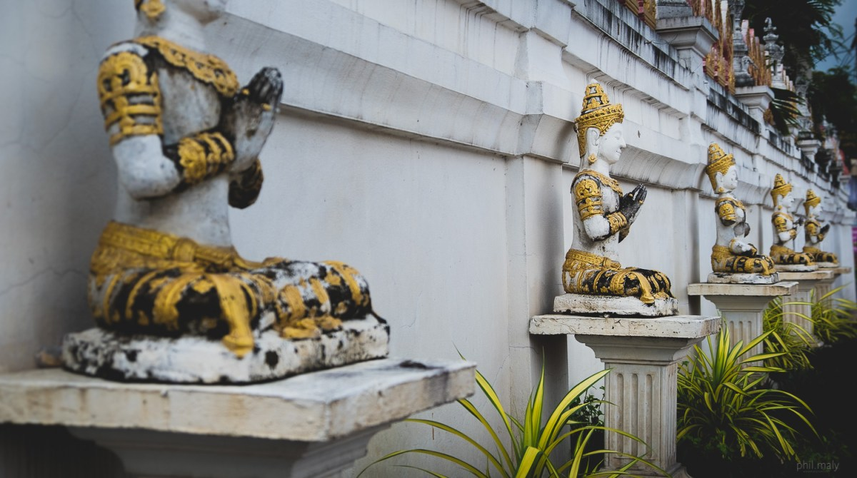 Row of golden Buddhas in the streets of Chiang Rai