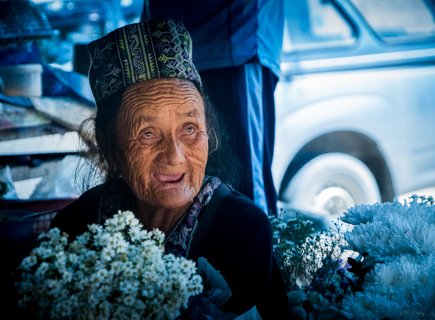 Old woman selling white flowers on a street market