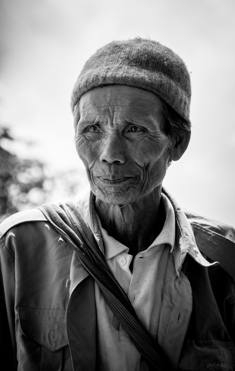 Street portrait of an old Thai man with a hat