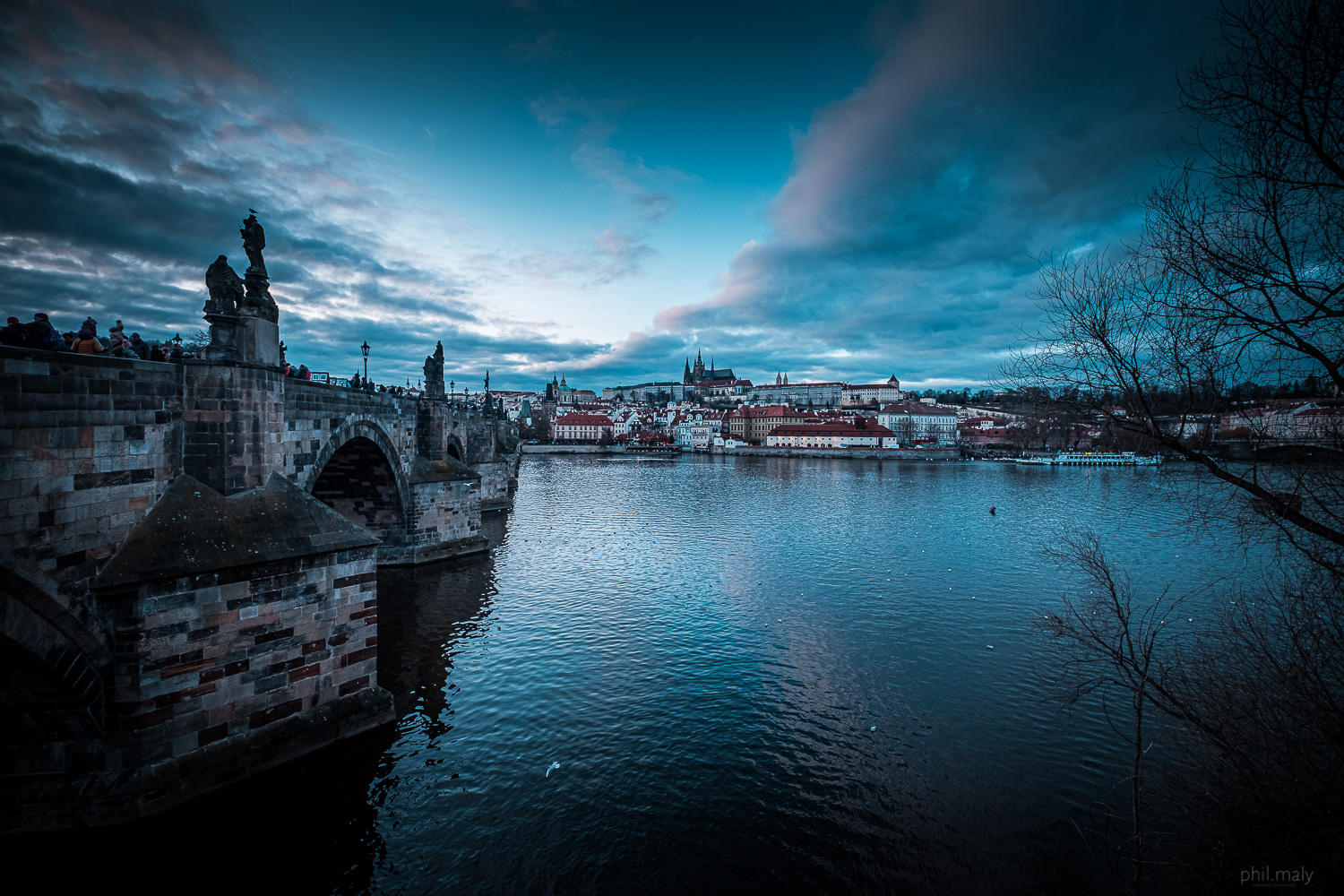 Charles bridge and the Prag castle at sunset with a pink sky