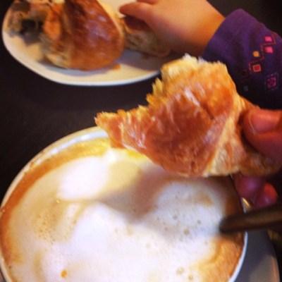 Kaffee und Croissant für Mama, dahinter: Croissant fürs Kind