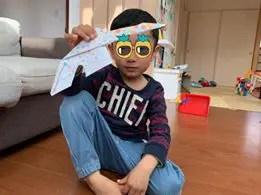 男の子が折り紙の作品を持っている様子
