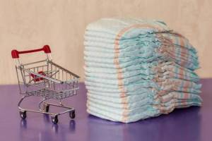 stack-of-diapers-or-nappies-and-mini-shopping-cart-parenthood-and-money