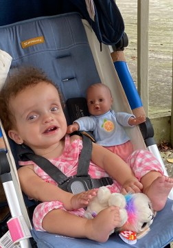 Hailey sitting in stroller doll to her right