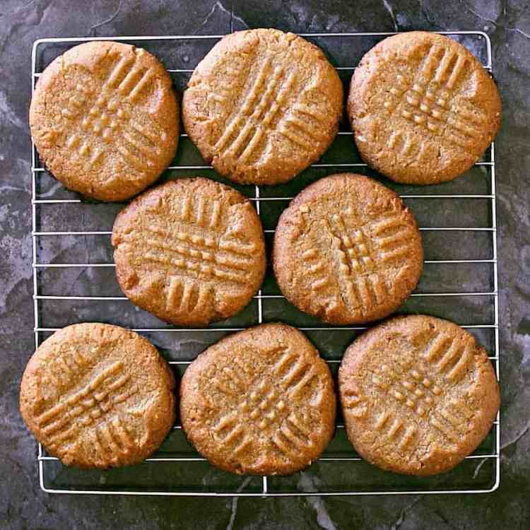 Peanut butter cookies cooling on a cooling rack.