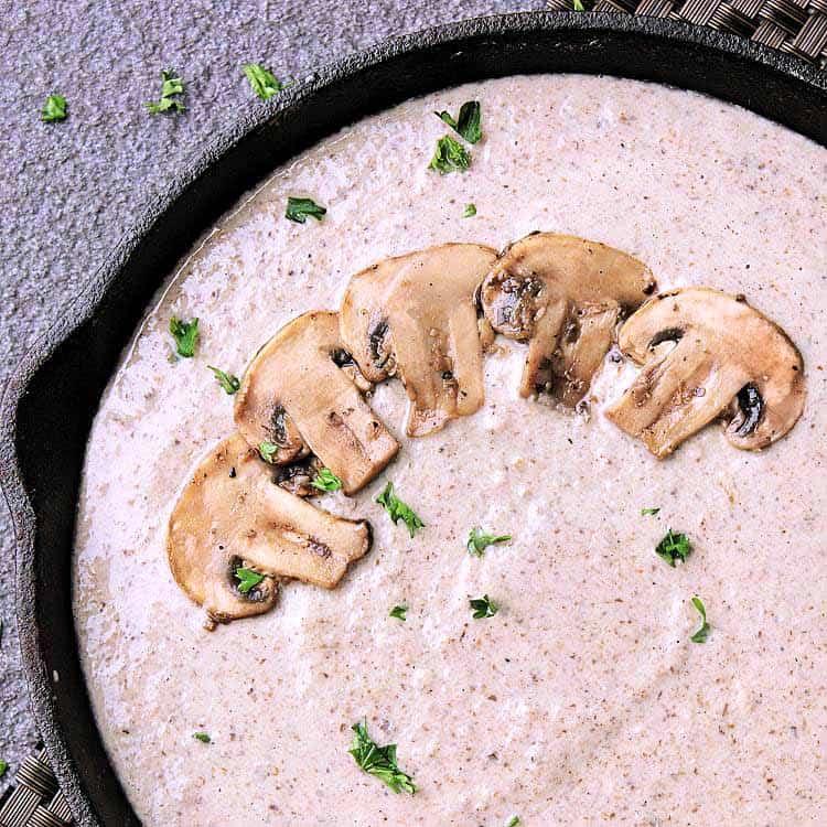Cast iron skillet filled with keto mushroom sauce.