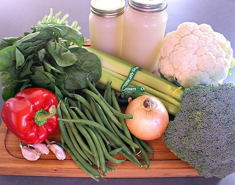 cutting board with whole broccoli, cauliflower, celery, onion, green beans, garlic, red pepper, spinach and bone stock.