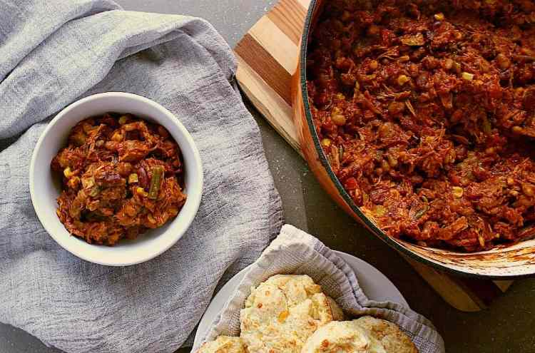 Big pot of leftover turkey chili next to cheese biscuits and a single bowl of chili.