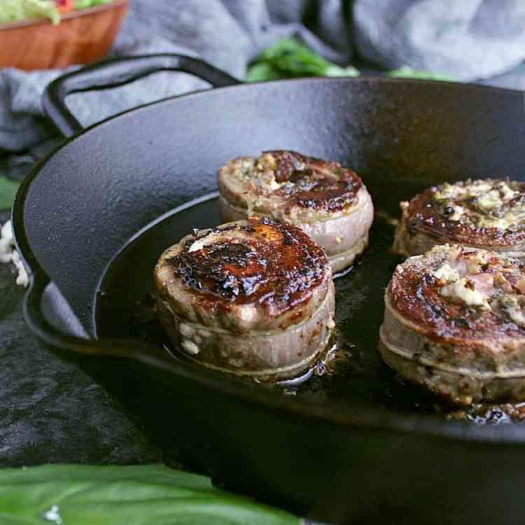 Cast iron skillet with four slices of stuffed flank steak, the tops have all been seared a beautiful brown.