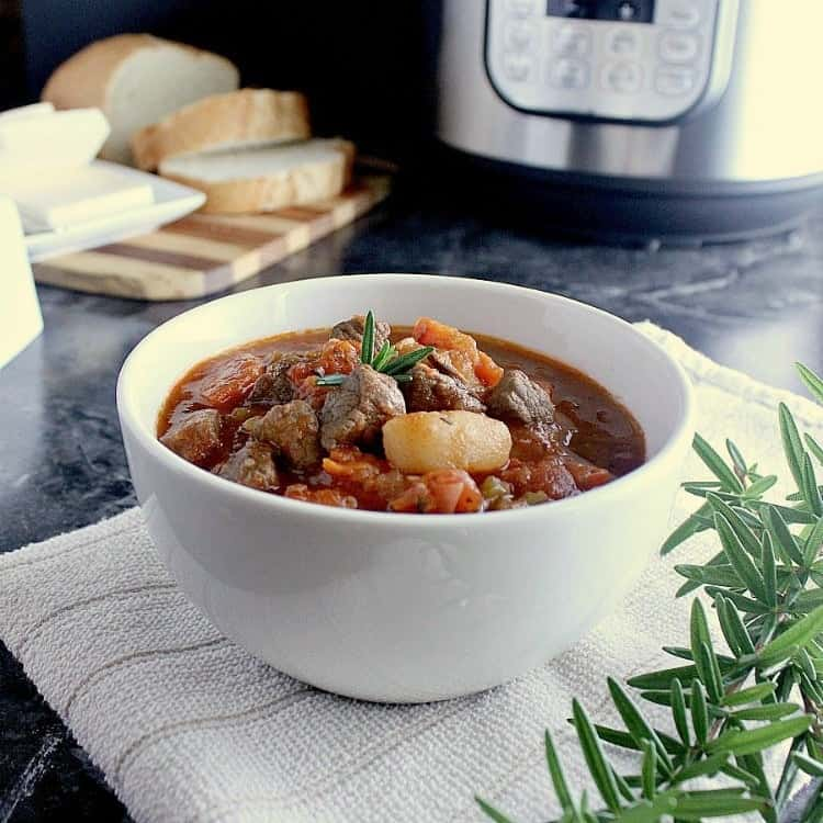 Bowl of Instant Pot Beef Stew with some fresh rosemary garnish.