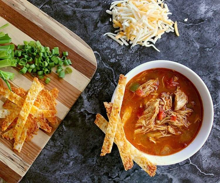 Bowl of Instant Pot Chicken Taco Soup and garnished with cheese crisps.