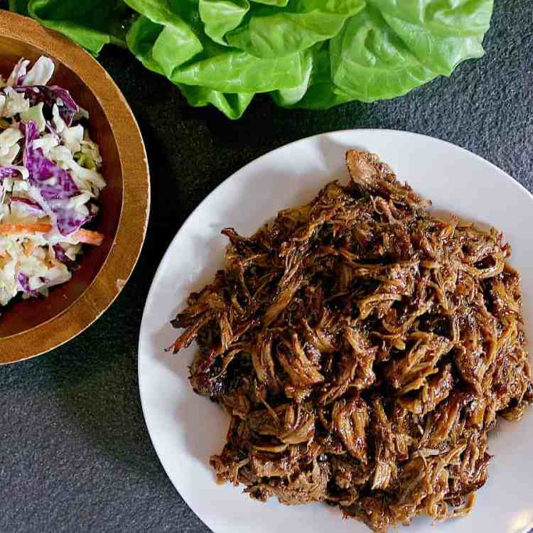 Big ol' dish of pulled pork next to a dish of coleslaw and butter lettuce leaves.