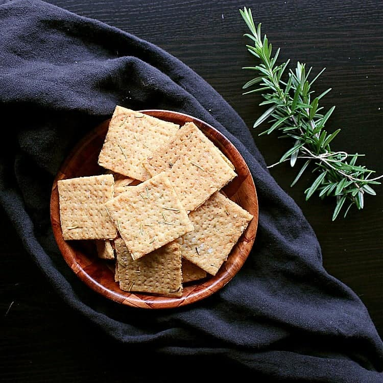 Bowl of low carb crackers next to a couple of fresh sprigs of rosemary.
