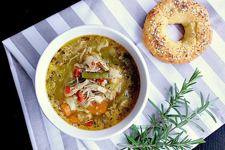 Bowl of soup next to a low carb bagel.