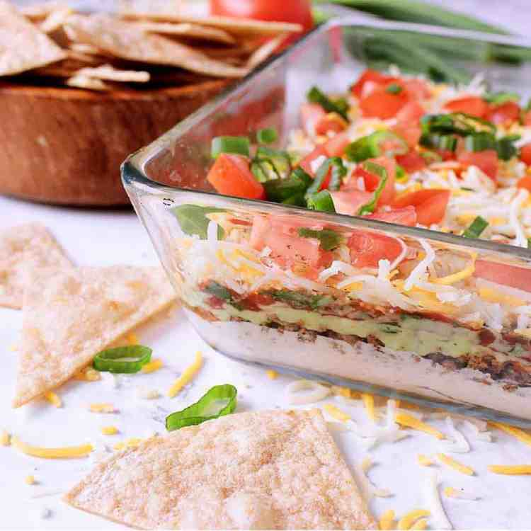 Dive into this low carb 7 layer dip for a fully loaded Mexican style appetizer perfect for potlucks, parties or a healthy snack!