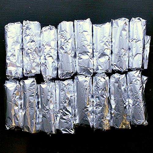 16 low carb breakfast burritos all wrapped in tin foil, ready to be frozen.