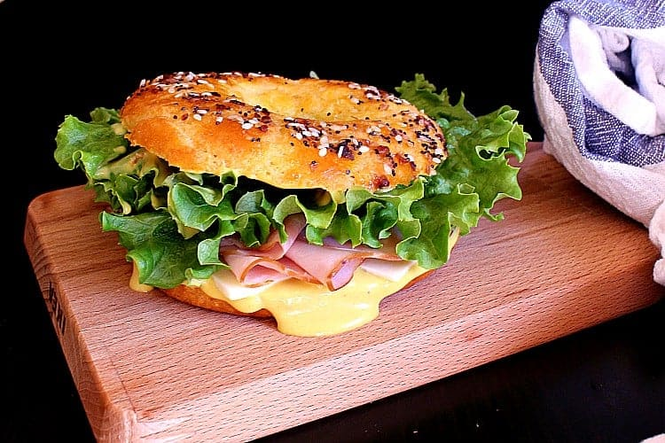 Ham and swiss sandwich on a low carb everything bagel with keto honey mustard dip.