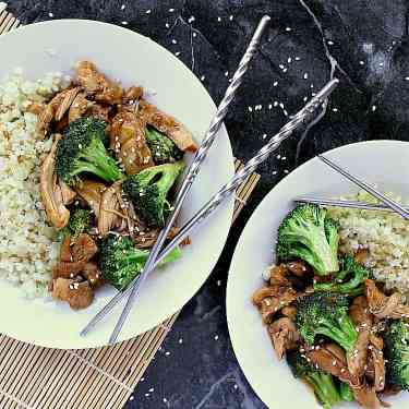 Two bowls of keto teriyaki chicken with cauliflower rice on the side.