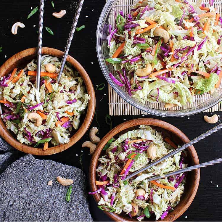 Two small bowls of low carb asian slaw, next to a larger serving bowl.