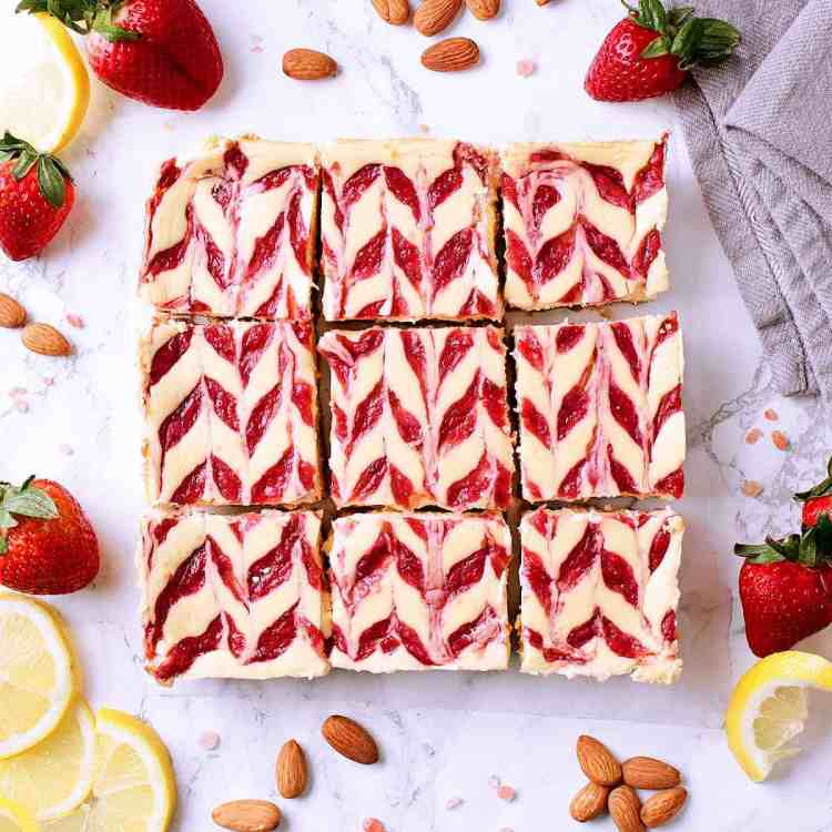 Strawberry Swirl Low Carb Cheesecake Bars, sliced into 9, surrounded by fresh strawberry and lemon slices.