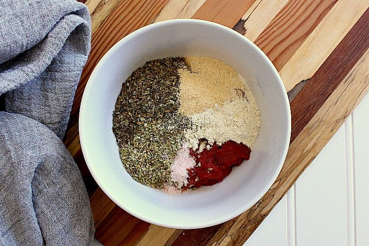 Bowl with tomato paste and the dried herbs, ready to be mixed.