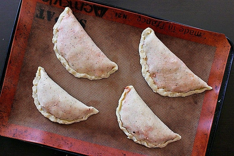 Four keto calzones on a baking sheet, ready to be placed inside the oven for baking.