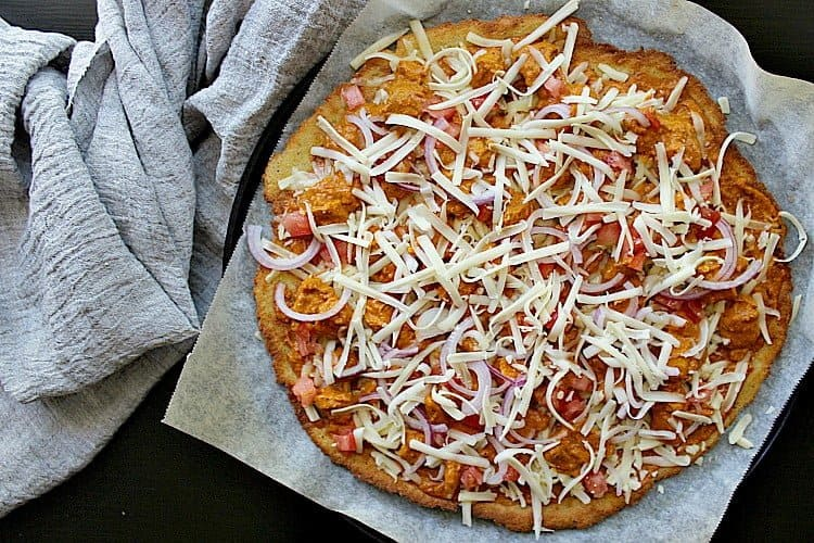 Fathead pizza crust topped with butter chicken, diced tomato, red onion and mozza, all ready for the oven.
