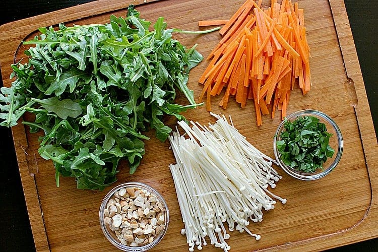 Cutting board filled with matchstick carrots, enoki mushrooms, cilantro, cashews and arugula.