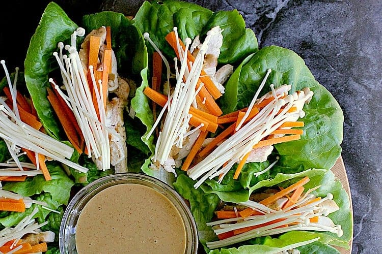 Butter lettuce leaves with chicken, peanut sauce, matchstick carrots and enoki mushrooms.