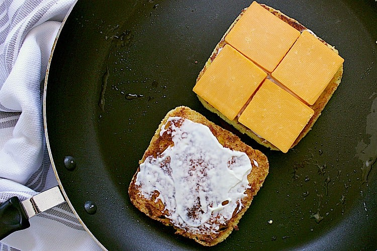 Two slices of bread on a skillet, both slices covered in mayo and one slice topped with cheddar cheese.