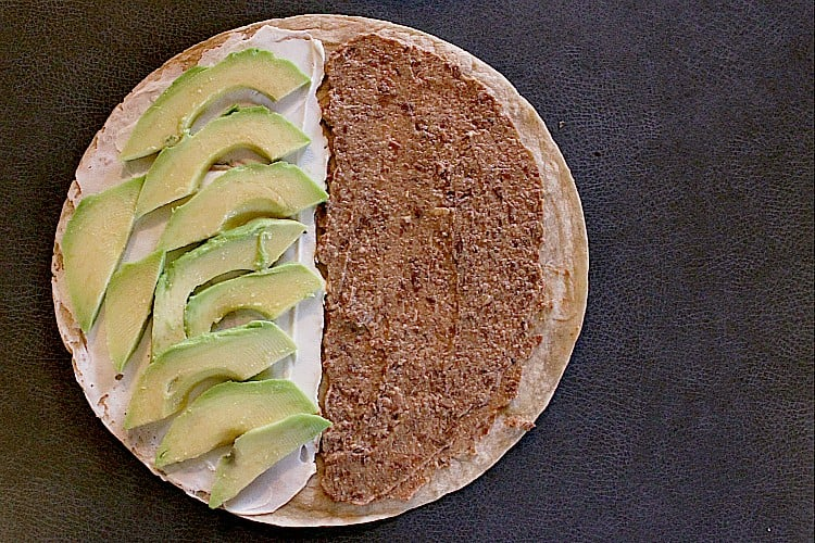 Low carb tortilla with low carb refried beans on one half and cream cheese and avocado on the other half.