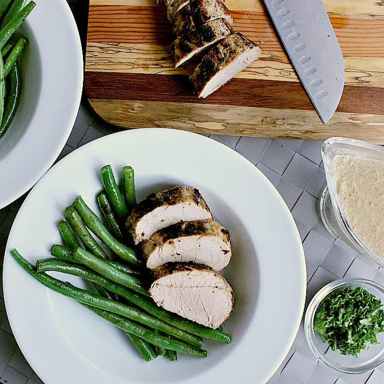 Plate of green beans with three slices of pork tenderloin. The plate is next to the remaining sliced pork, mushroom sauce and minced parsley.