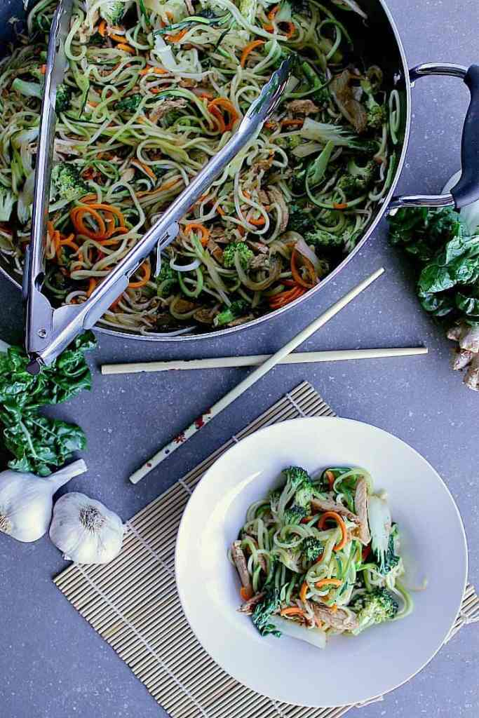 Bowl of zucchini noodle stir fry next to the skillet full of zucchini noodle stir fry.
