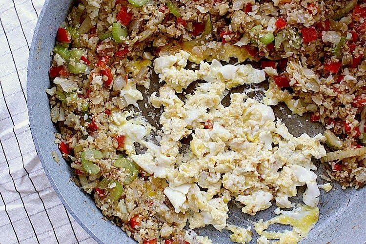 Cauliflower fried rice moved to the sides of the skillet with scrambled eggs in the middle.