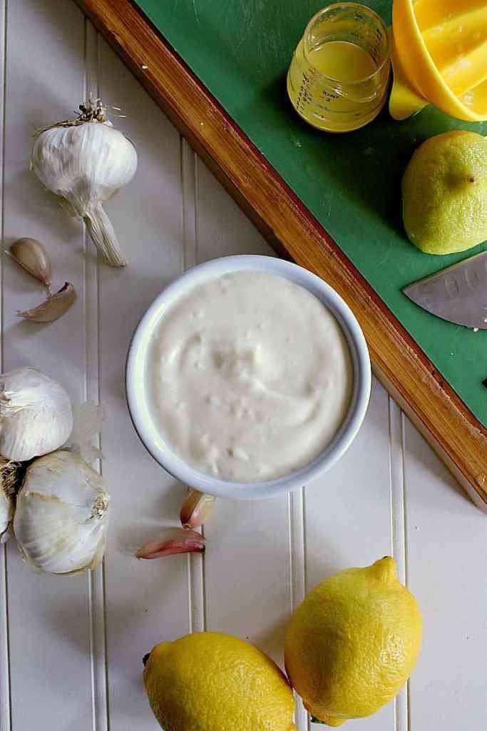 Freshly made bowl of garlic aioli next to some garlic, sea salt and lemons.
