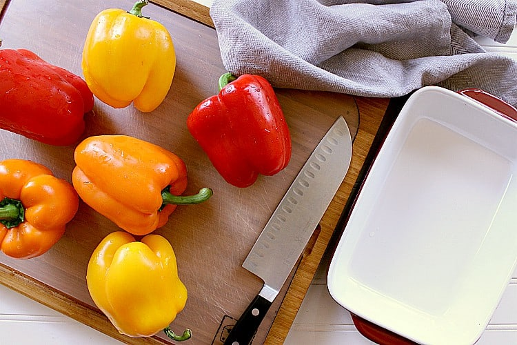 6 washed bell peppers next to an empty baking dish.