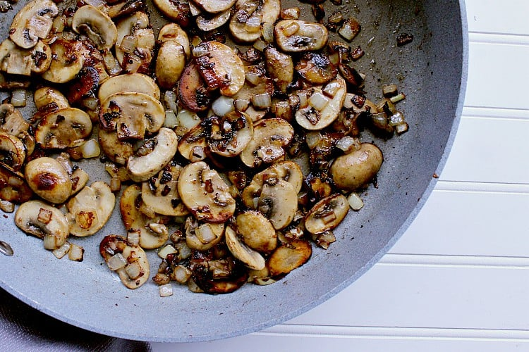 Skillet with fried mushrooms and onions.